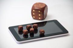 La tableta con dados de madera grandes y un pequeño de madera corta en cuadritos en displa Foto de archivo