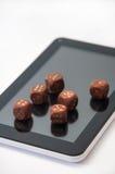 La tableta con dados de madera grandes y un pequeño de madera corta en cuadritos en displa Imagenes de archivo