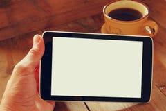 La tableta de Digitaces con la pantalla aislada en varón entrega el fondo de la tabla y la taza de café de madera Fotos de archivo