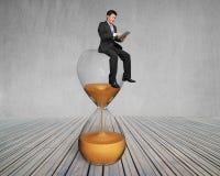 La tableta del uso del hombre de negocios y se sienta en el vidrio de la hora imágenes de archivo libres de regalías