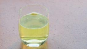 La tableta efervescente amarilla disuelve en el vidrio de agua metrajes