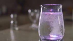 La tableta efervescente cae en un vidrio con agua y las luces coloridas chispeantes metrajes