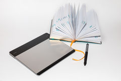 La tableta gráfica con la pluma y el cuaderno Imagenes de archivo