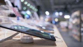 La tableta moderna en la tienda de la electrónica, varios dispositivos se estableció para la exhibición en la sala de exposición almacen de video