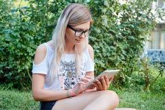 La tableta Muchacha hermosa que trabaja en una tableta Tecnologías modernas Mujer con una tableta en la naturaleza Imagen de archivo