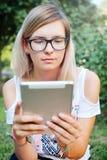 La tableta Muchacha hermosa que trabaja en una tableta Tecnologías modernas Mujer con una tableta en la naturaleza Fotos de archivo libres de regalías