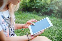 La tableta Muchacha hermosa que trabaja en una tableta Tecnologías modernas Mujer con una tableta en la naturaleza Fotografía de archivo