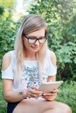 La tableta Muchacha hermosa que trabaja en una tableta Tecnologías modernas Mujer con una tableta en la naturaleza Foto de archivo