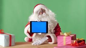 La tableta sonriente de la demostración de Santa Claus con la pantalla azul in camera, los regalos en la tabla, pone verde chroma almacen de video