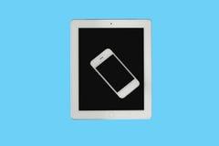 La tableta y el smartphone se aísla en fondo azul Foto de archivo