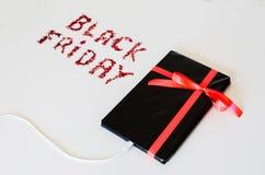 La Tablette électronique a enveloppé le boîte-cadeau avec une corde rouge et un texte de Black Friday Image stock
