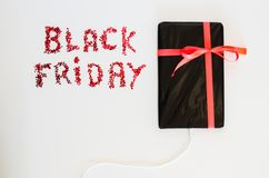La Tablette électronique a enveloppé le boîte-cadeau avec une corde rouge et un texte de Black Friday Photographie stock libre de droits