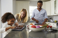 La tablette d'utilisation de maman et de fille, et le papa prépare la nourriture Photos stock