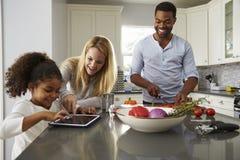 La tablette d'utilisation de maman et de fille, et le papa prépare la nourriture Photos libres de droits