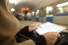 La Tablette dans des mains femelles montrant le souterrain tracent dedans Image stock