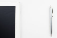 La tablette et un métal moderne argentent le stylo sur un espace blanc de copie de fond Photos libres de droits