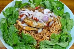 La tagliatella istantanea piccante con il pesce ha inscatolato l'insalata sul piatto Immagine Stock