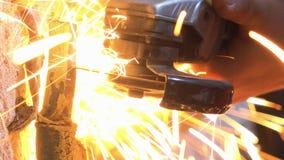 La tagliatrice circolare usata uomo è tagliata il tubo con il lotto delle scintille stock footage
