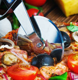 La taglierina taglia una pizza fresca con i funghi Fotografia Stock Libera da Diritti