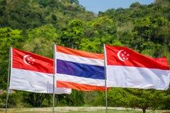 La Tailandia e Singapore inbandiera saltato sull'asta della bandiera con più forrest Fotografia Stock
