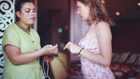 La Tailandia, Koh Samui 12 dicembre 2015 L'estetista consiglia il cliente ed esamina le sue mani in salone 1920x1080 stock footage
