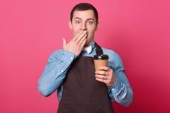 La taille vers le haut du tir du barman masculin étonné couvre la bouche de paume, entend des nouvelles choquantes de café ou le  photo stock