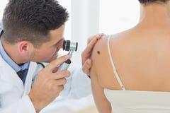 La talpa d'esame di medico sopra appoggia della donna Fotografia Stock