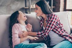 La tante délicieuse heureuse utilisant la chemise à carreaux et les jeans est tickl Image libre de droits