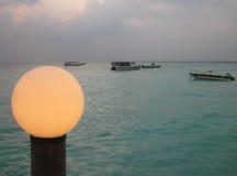 La tarde con los barcos y el punto se encienden en la costa del océano Imagen de archivo