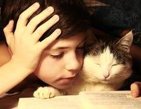 La tarde del muchacho leyó el libro con el gato Fotografía de archivo