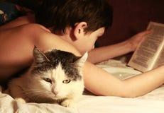 La tarde del muchacho leyó el libro con el gato Foto de archivo