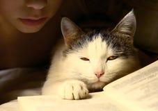 La tarde del muchacho leyó el libro con el gato Imagenes de archivo