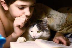 La tarde del muchacho leyó el libro con el gato Imagen de archivo libre de regalías