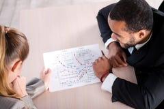 La tarea El hombre de negocios africano ve gráficos en el papel Fotos de archivo libres de regalías