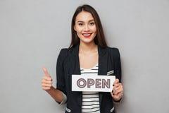La targhetta felice della tenuta della donna di affari aperta e la rappresentazione sfogliano su Immagine Stock Libera da Diritti