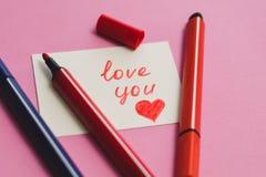 La tarjeta blanca con la palabra 'ama le 'y a los marcadores coloreados en un fondo rosado imagen de archivo libre de regalías