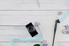 La tarjeta blanca en blanco, la pluma oblicua y la botella de tinta adornan con las flores de papel del tono azul foto de archivo