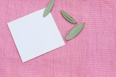 La tarjeta blanca en un verde rosado hecho punto de las lanas se va Foto de archivo