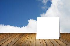 La tarjeta blanca puso el escritorio de madera o el piso de madera en fondo del cielo azul y de la nube uso para el presente o mo Imágenes de archivo libres de regalías