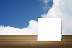 La tarjeta blanca puso el escritorio de madera o el piso de madera en fondo del cielo azul y de la nube uso para el presente o mo Foto de archivo libre de regalías