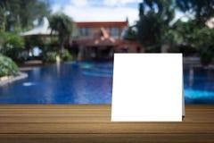 La tarjeta blanca puso el escritorio de madera o el piso de madera en piscina borrosa en el fondo del centro turístico uso para e Imágenes de archivo libres de regalías