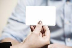 La tarjeta blanca vacía está llevando a cabo los fingeres y la mano fotos de archivo libres de regalías