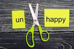La tarjeta con el texto infeliz, tijeras cortó la O.N.U de la palabra el concepto de éxito y de felicidad lifestyle imagen de archivo