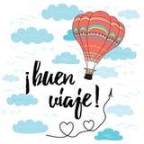 La tarjeta con viaje feliz del texto en lengua española adornó el globo del aire caliente Imagen de archivo libre de regalías