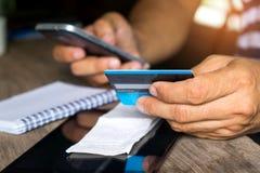 La tarjeta de crédito en línea del control encarga de los smartphones, cre en línea de la paga Imagen de archivo