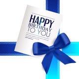 La tarjeta de cumpleaños con la cinta azul y el cumpleaños mandan un SMS Fotos de archivo