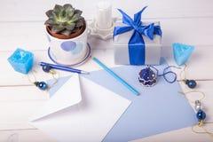 La tarjeta de felicitación azul en blanco con blanco envuelve, regalo, succulent, y las decoraciones de la Navidad Endecha plana, Imágenes de archivo libres de regalías