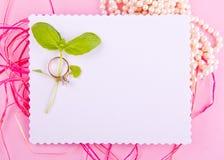 La tarjeta de felicitación blanca con el borde ondulado se adorna con los anillos de bodas y plan verde en fondo rosado Foto de archivo