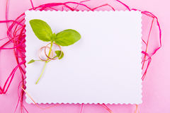 La tarjeta de felicitación blanca con el borde ondulado se adorna con los anillos de bodas y plan verde en fondo rosado Imagen de archivo