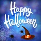 La tarjeta de felicitación de Halloween con el sombrero de la bruja, las arañas enojadas y 3d cepillan las letras en fondo azul c Imagen de archivo libre de regalías